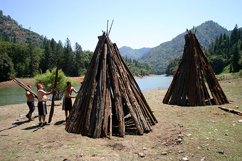 Winnemem men build two bark huts on the banks of the McCloud River for the puberty ceremony for two young women. Sacred sites related to this ceremony will be permanently submerged if Shasta Dam is raised. © 2010 Christopher McLeod